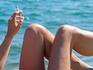 woman relaxes by the sea smoking  cigarette